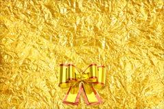 Glanzend geel bladgoud en lint op Glanzende folie Stock Fotografie