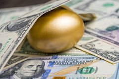 Glanzend gouden ei onder stapel van van de dollarbankbiljetten van de V.S. Amerika het geldmetafoor van het vinden van de ongeloo royalty-vrije stock foto