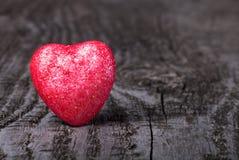 Glanzend rood hart op oude houten achtergrond Stock Foto