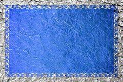 Glanzend zilveren kader met een patroon op de blauwe folieachtergrond Royalty-vrije Stock Foto's