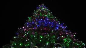 Glanzende hoge die Kerstmisspar met slingers en multi-colored ballen tegen de nachthemel wordt verfraaid weinig sneeuw valt stock videobeelden