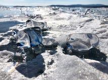 Glanzende ijsblokjes De mening van de avond Barsten op de oppervlakte van het blauwe ijs Bevroren meer Baikal in de winterbergen  stock fotografie