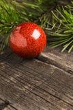 Glanzende rode christmassbal met de groene tak van de sparpijnboom stock afbeelding