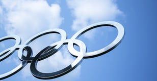 Glanzende roestvrij staal olympische ringen met blauwe hemel stock afbeelding