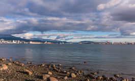 Glanzende strand zijrotsen onder een laag wolken Stock Afbeeldingen