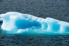 Glanzende turkooise Ijsberg die door turkoois glanzend water, Groenland wordt omringd stock foto's