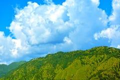 Glanzende wolken met blauwe hemel en groene bergen Stock Foto