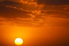 Glanzende zon in een oranje zonsondergang stock foto