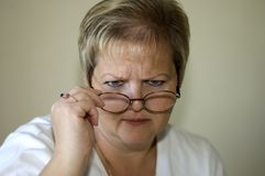 The Glare. Blond woman with glare look over eyeglasses Stock Photos