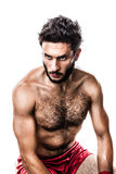 Glaring. A very muscular young boxer with red trunks and hand wraps isolated over white background Stock Photography