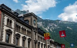Glarus, switzerland. old building with clock and swiss canton flags. Infront of mountain scenery royalty free stock images