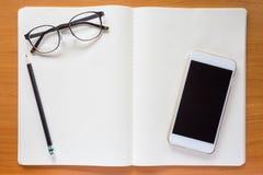 Glasögon blyertspenna, mobiltelefon, anteckningsbok Royaltyfria Bilder