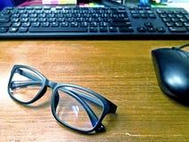 Glasögon förlägger på det gamla träskrivbordet med suddig datorkeyboa royaltyfri fotografi