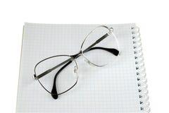 Glasögon ligger på en anteckningsbok Fotografering för Bildbyråer