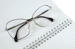 Glasögon ligger på en anteckningsbok Royaltyfri Fotografi