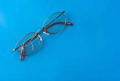 Glasögon med den spruckna linsen på skinande blå bakgrund Arkivbild