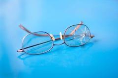 Glasögon med den spruckna linsen på skinande blå bakgrund Fotografering för Bildbyråer