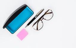 Glasögon med fallet och penna och papper Fotografering för Bildbyråer