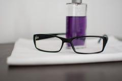 Glasögon med parfum på tabellen Royaltyfri Bild