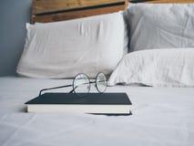 Glasögon och boken i sovrummet för att läsa och kopplar av royaltyfri fotografi