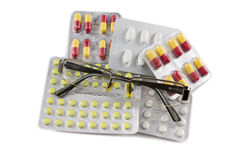 Glasögon och preventivpillerar som isoleras på vit bakgrund Arkivfoton