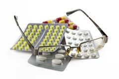 Glasögon och preventivpillerar som isoleras på vit bakgrund Royaltyfri Bild