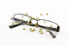 Glasögon och preventivpillerar som isoleras på vit bakgrund Royaltyfri Fotografi