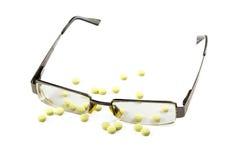 Glasögon och preventivpillerar som isoleras på vit bakgrund Arkivbilder