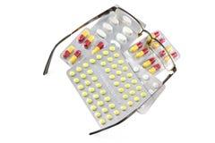 Glasögon och preventivpillerar som isoleras på vit bakgrund Royaltyfria Foton