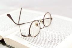 Glasögon på den öppna boken Arkivfoto
