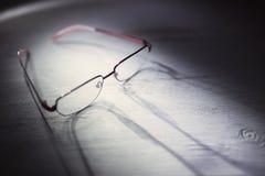 Glasögon på en trätabell Arkivfoto