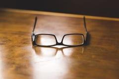 Glasögon på en wood tabell Arkivfoto