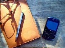 Glasögon, penna, mobiltelefon och anteckningsbok Arkivfoto