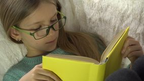 Glasögonbarnläsebok på soffan, flickastående som studerar i säng, lagledare 4K arkivfilmer