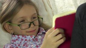 Glasögonbarnläsebok på soffan, flickastående som studerar i säng, lagledare 4K lager videofilmer