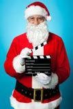 Glasögonprydda Santa som rymmer en clapperboard Arkivbild