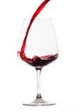 红葡萄酒涌入了glas (空白背景) 库存图片