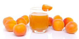 Glas abrikozensap met abrikozen wordt omringd die Stock Fotografie