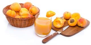Glas abrikozensap met een mand van abrikozen en gesneden apri Royalty-vrije Stock Foto's