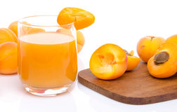 Glas abrikozensap met gehele en gesneden abrikozen Royalty-vrije Stock Afbeelding