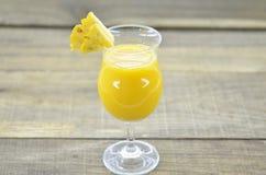 Glas Ananassaft, frische Ananas und Scheiben auf hölzernem Lizenzfreie Stockbilder