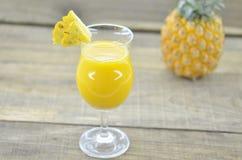 Glas Ananassaft, frische Ananas und Scheiben auf Holztisch Lizenzfreie Stockfotografie
