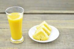 Glas ananassap, de verse plakken van de ananasbesnoeiing op houten lijst Stock Foto's