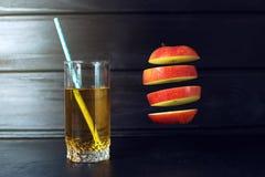 Glas appelsap met het gesneden appel hangen in lucht Stock Foto