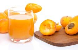 Glas Aprikosensaft mit den ganzen und geschnittenen Aprikosen Lizenzfreies Stockbild