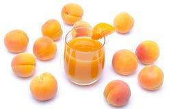 Glas Aprikosensaft umgeben mit Aprikosen Lizenzfreie Stockfotos
