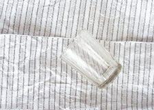 Glas auf einem Hintergrund der zerknitterten DNA-Sequenz Stockbilder
