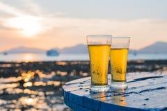 Glas Bier auf einem Sonnenuntergang Stockbild