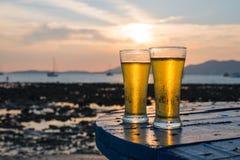 Glas Bier auf einem Sonnenuntergang Lizenzfreies Stockfoto