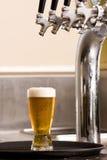 Glas Bier auf einem Tellersegment Stockbilder